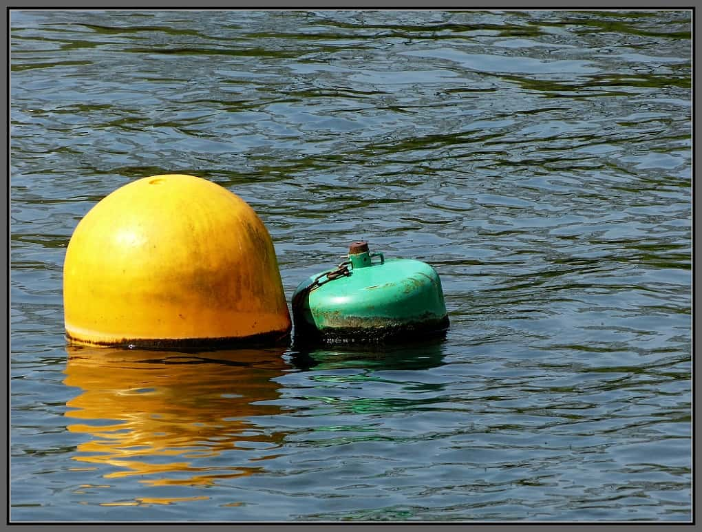 A yellow and a green coloured bouy in a river