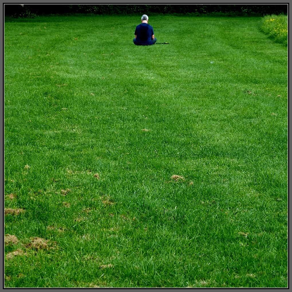 Someone sitting alone in a field