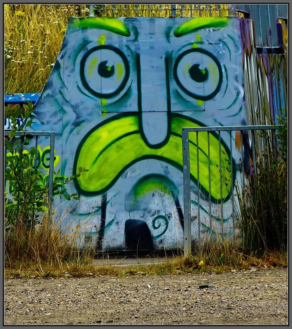 Graffiti painting of a grumpy face.